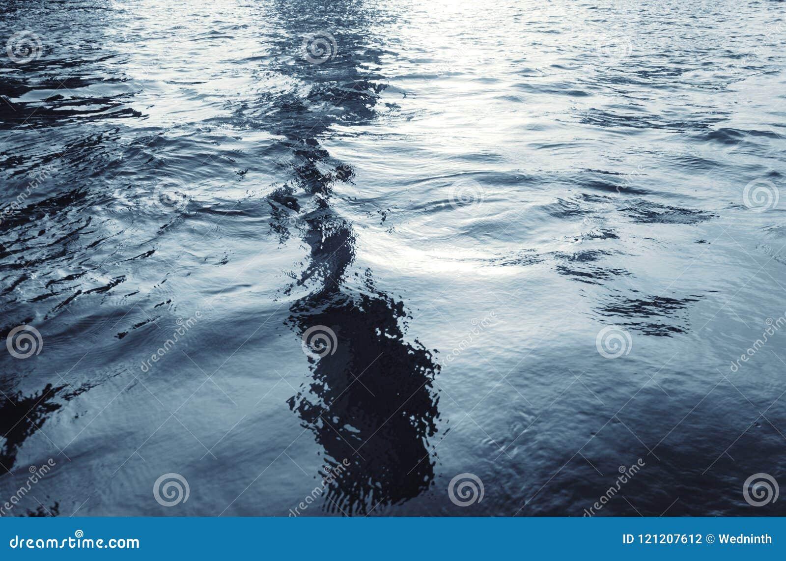 Wodna powierzchnia z czochrami i świateł słonecznych odbiciami