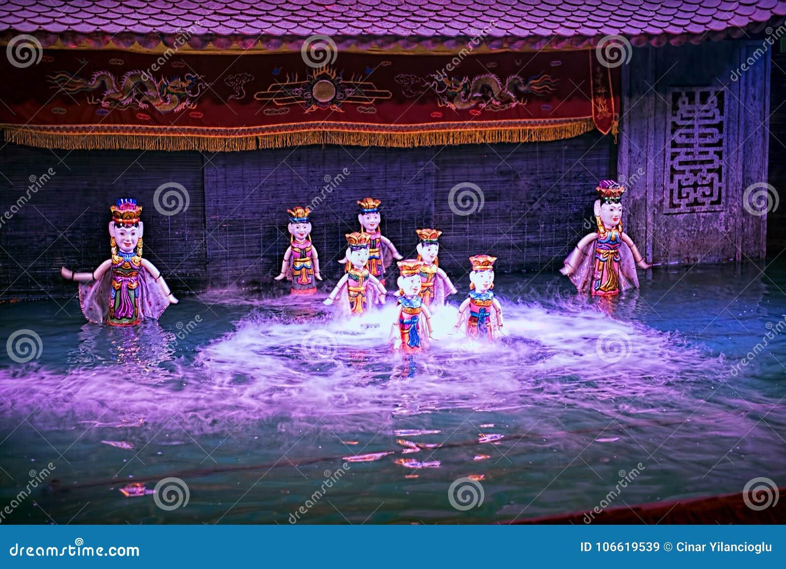 Wodny kukiełkowy przedstawienie w Wietnam pod purpurowymi światłami