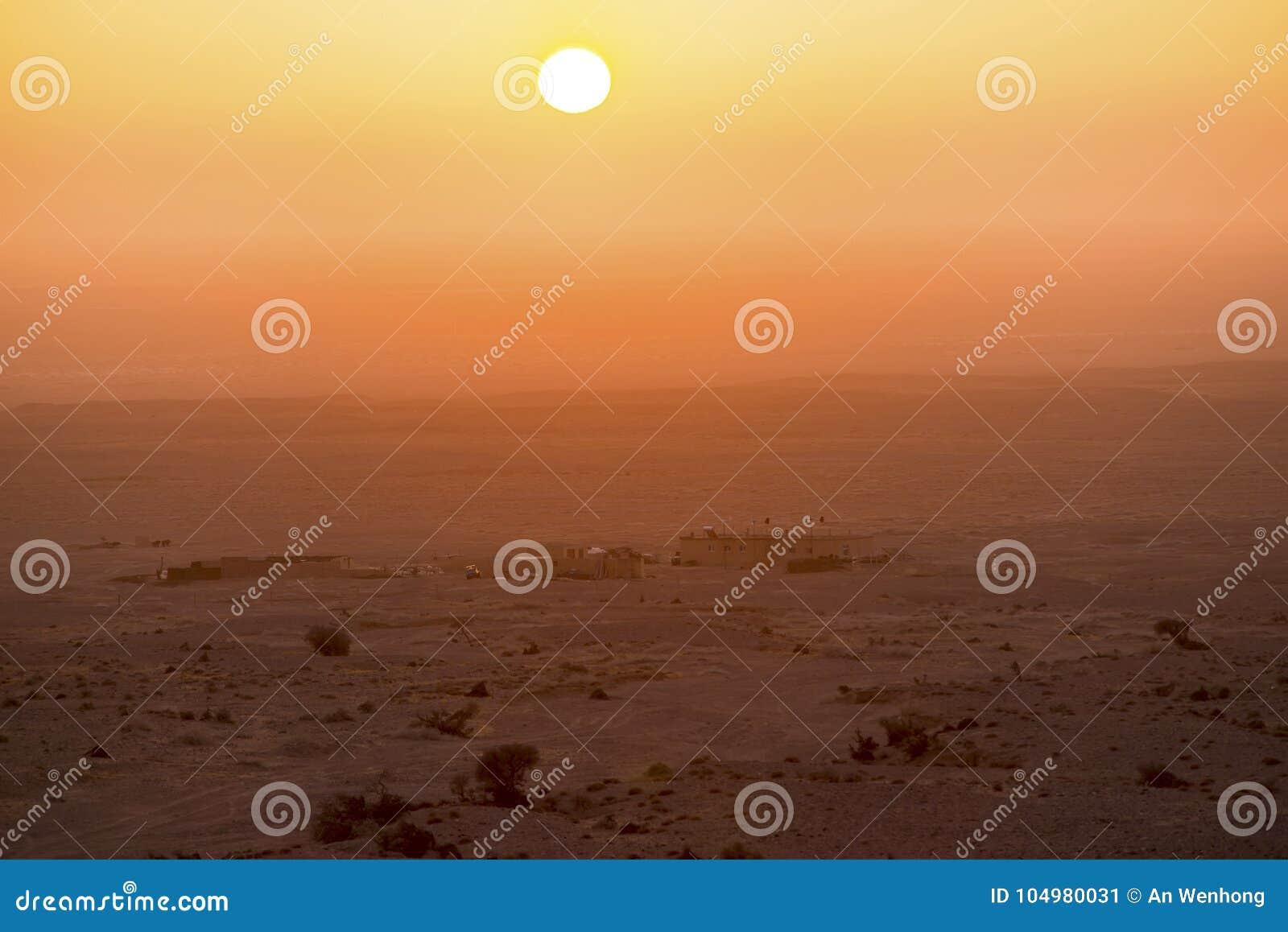 Woestijnzonsopgang en veehoeders` s huizen