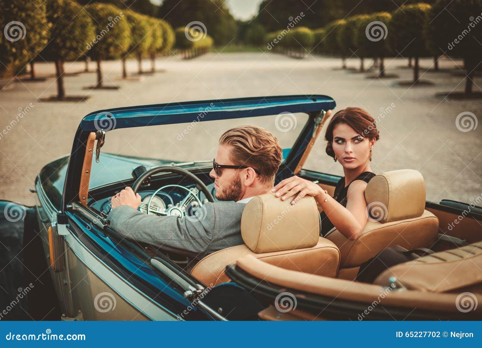 Wohlhabende Paare im klassischen Kabriolett