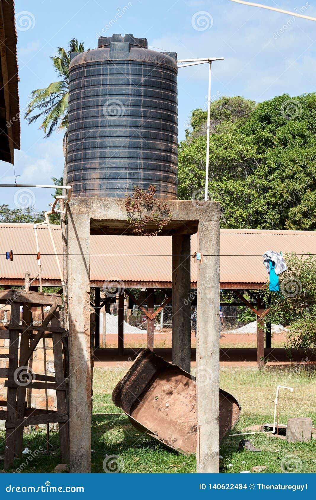 Wohnplastikwasserversorgungsbehälter auf Hochbahnsteig in Lethem Guyana