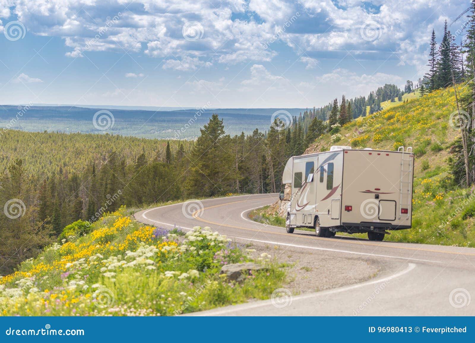 Wohnwagen, der hinunter Straße in der schönen Landschaft unter Kiefer fährt