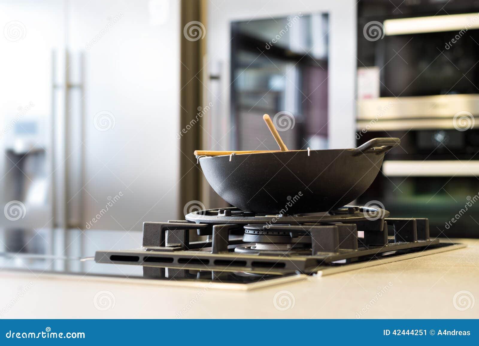 Wok de los tallarines en estufa de gas en workplate