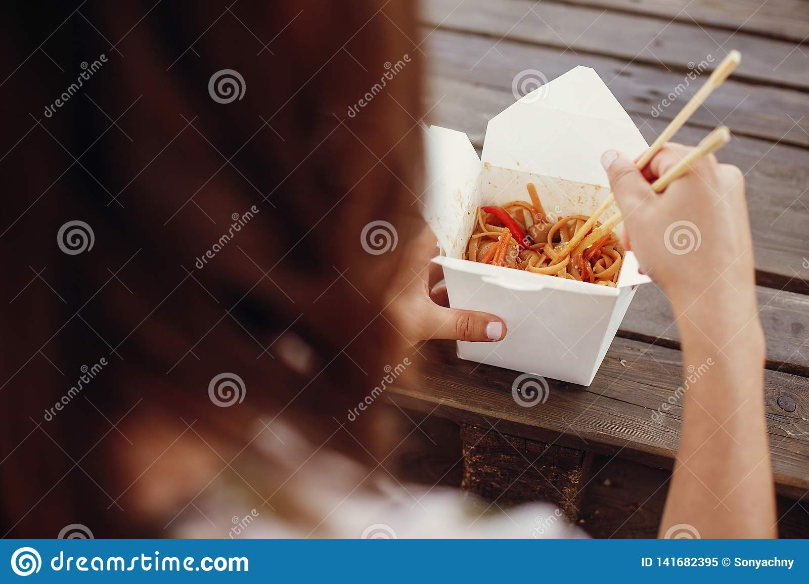 Wok with noodles and vegetables in carton box to go and bamboo chopsticks. Traditional Asian cuisine. Asian Street food festival.