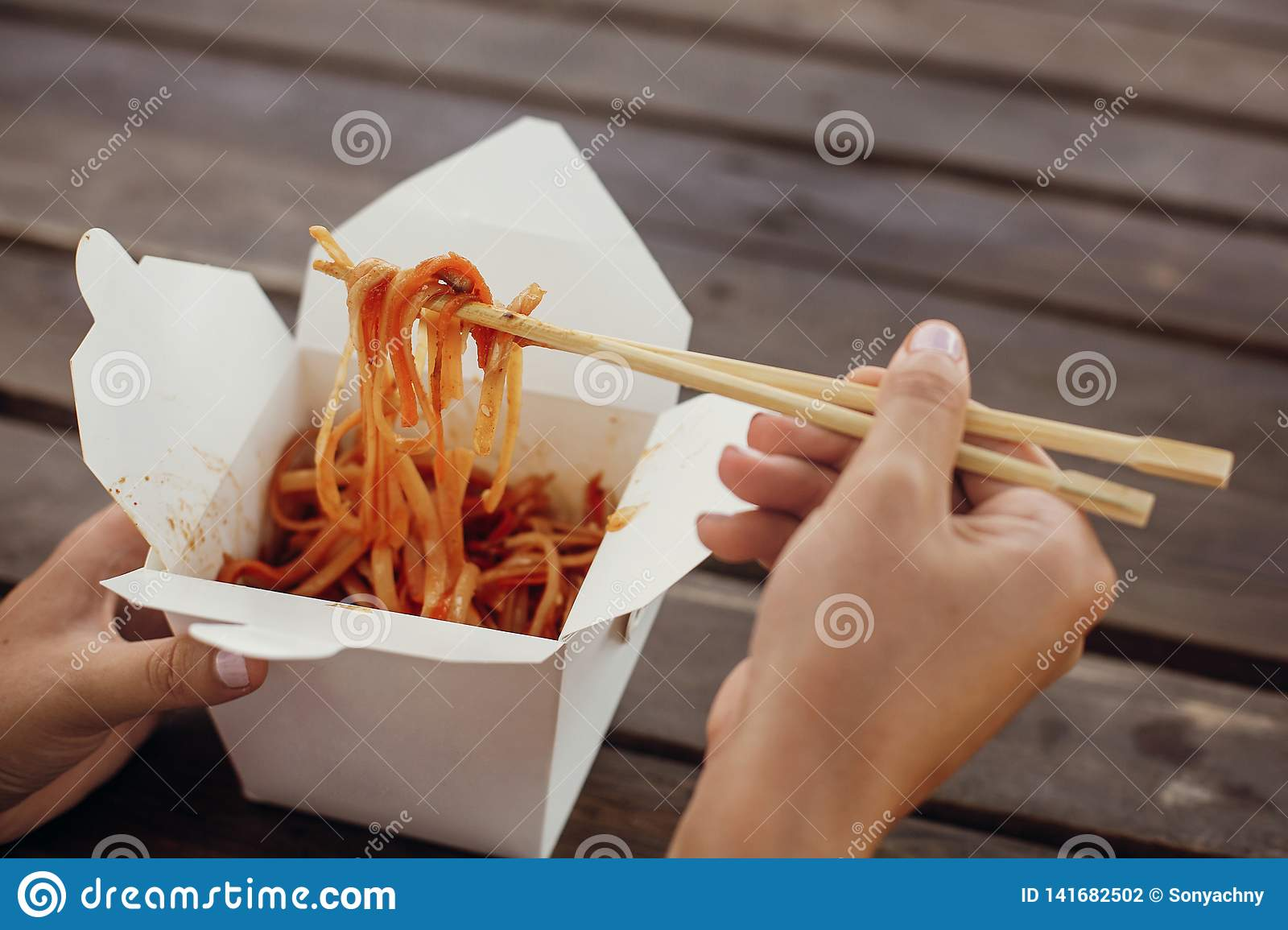 Wok With Noodles And Vegetables In Carton Box To Go And Bamboo