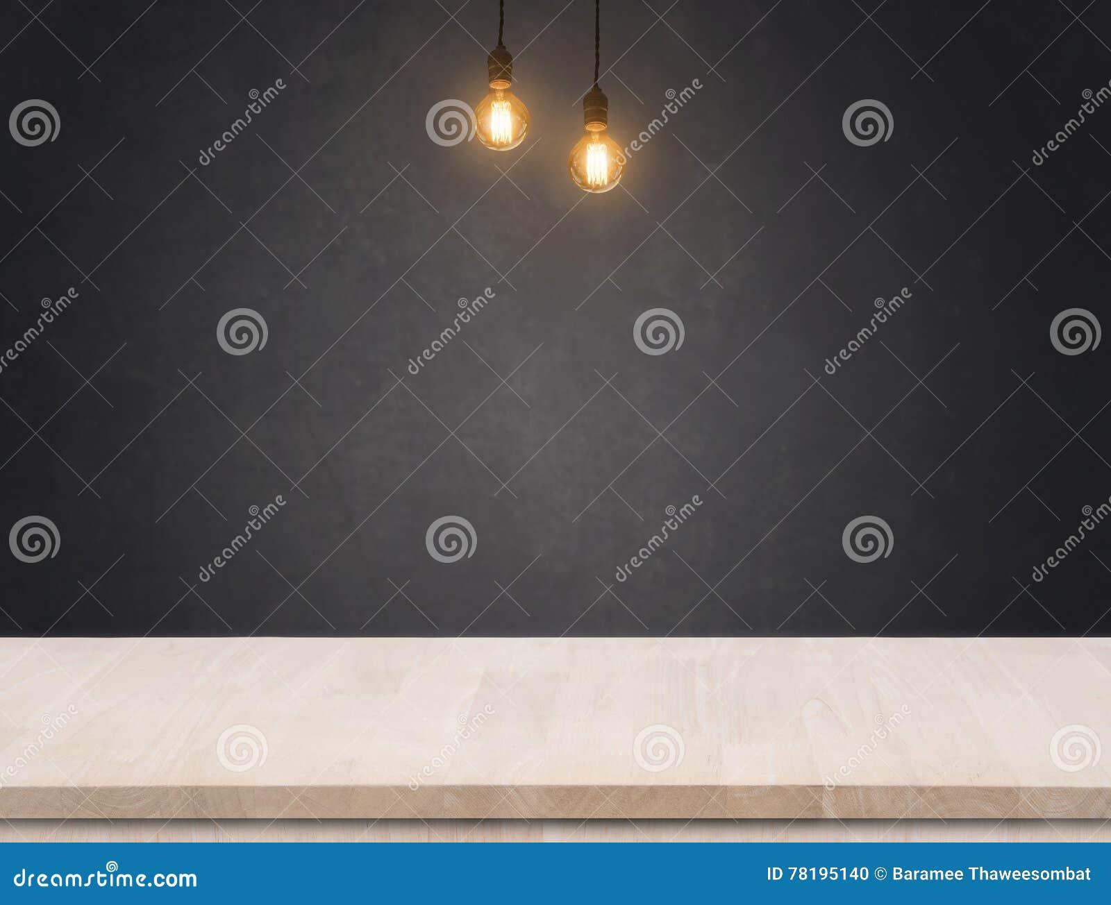 Wolfram żarówka z czerń cementu ściany tłem i drewno stołem