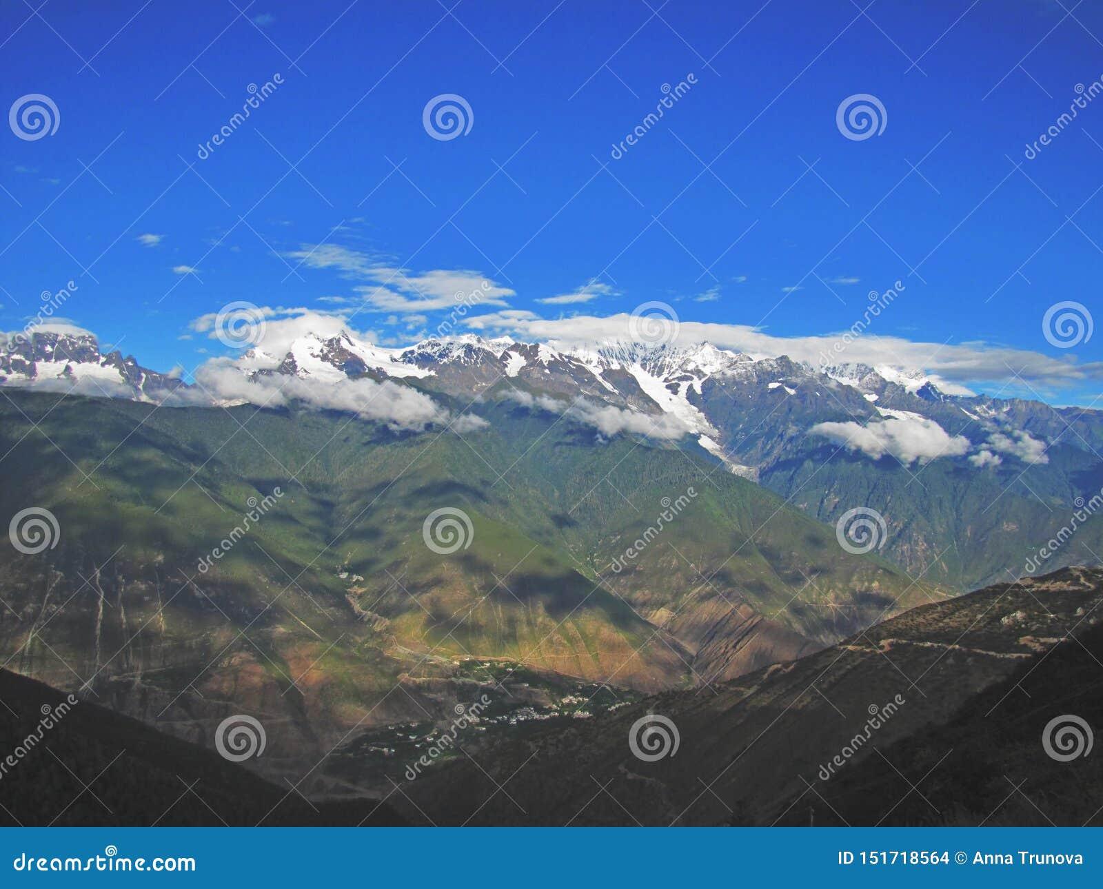 Wolken in blauwe hemel over de sneeuwbergen