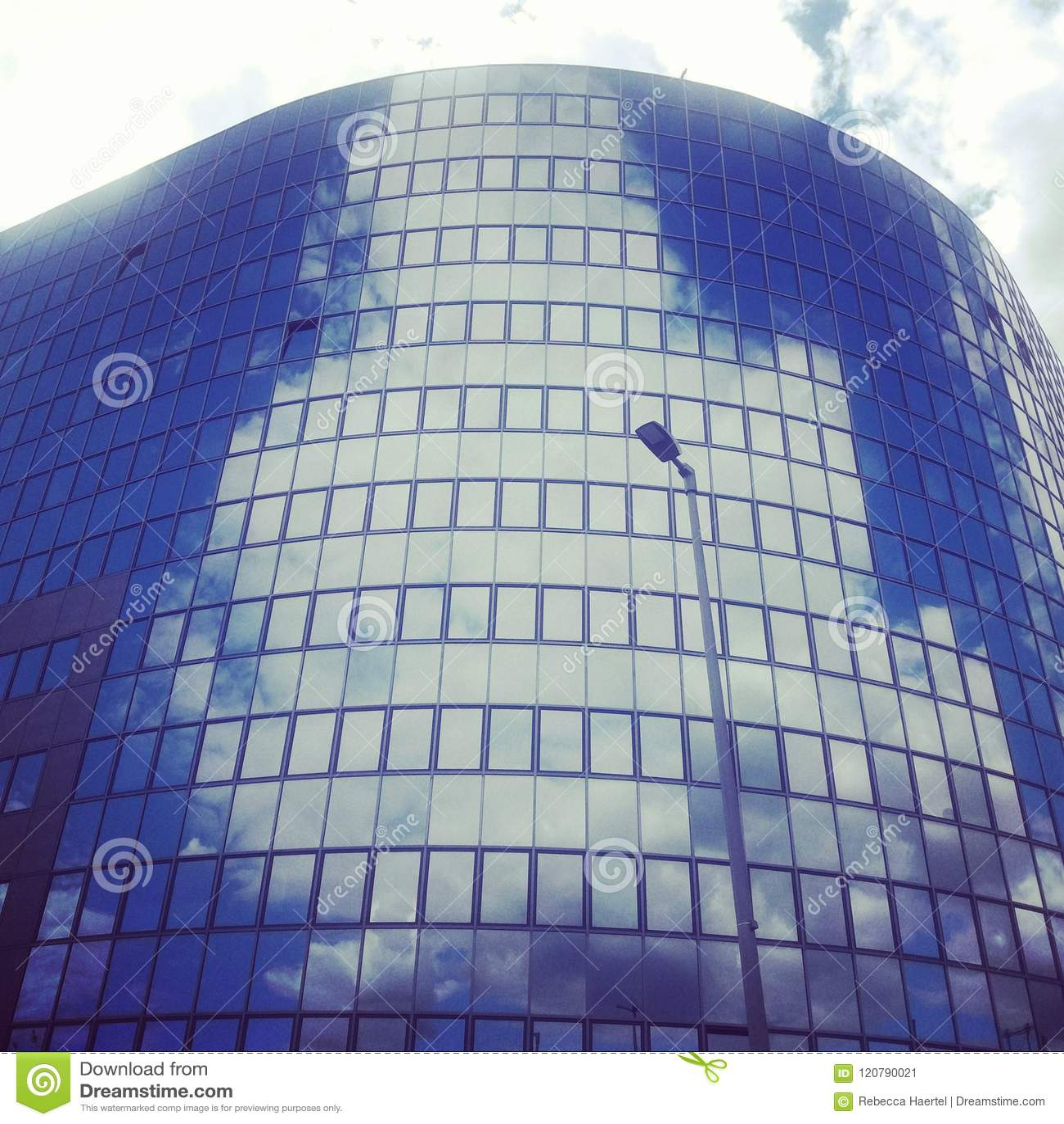 Wolken, die im modernen Bürogebäude sich reflektieren