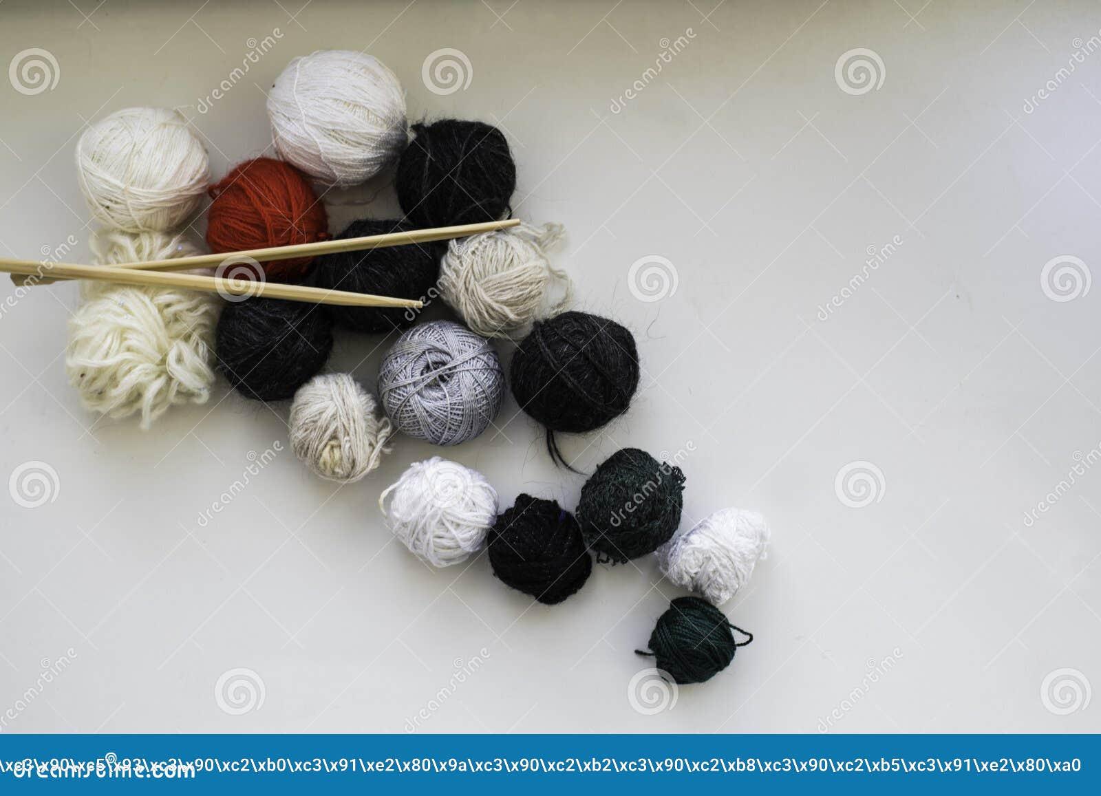 Wollen ballen en houten breinaalden op de neutrale achtergrond Vlak leg