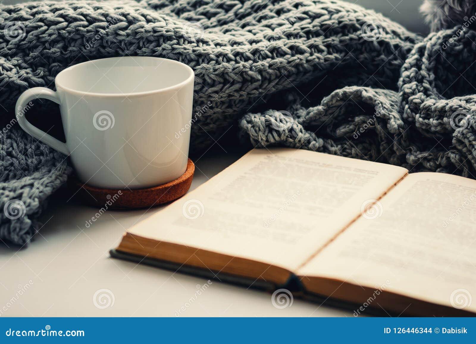 Wollen sjaal, een kop thee en een boek op de vensterbank Hygge en comfortabel de herfstconcept