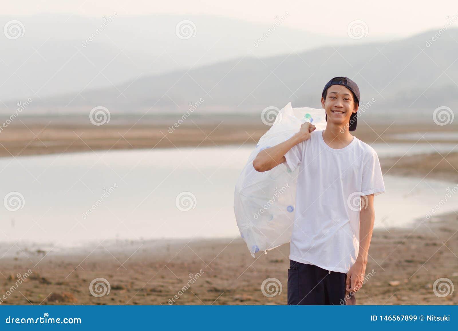 Wolontariusz czyści w górę rzecznego podnosi w górę klingerytu i niszczy na ziemi