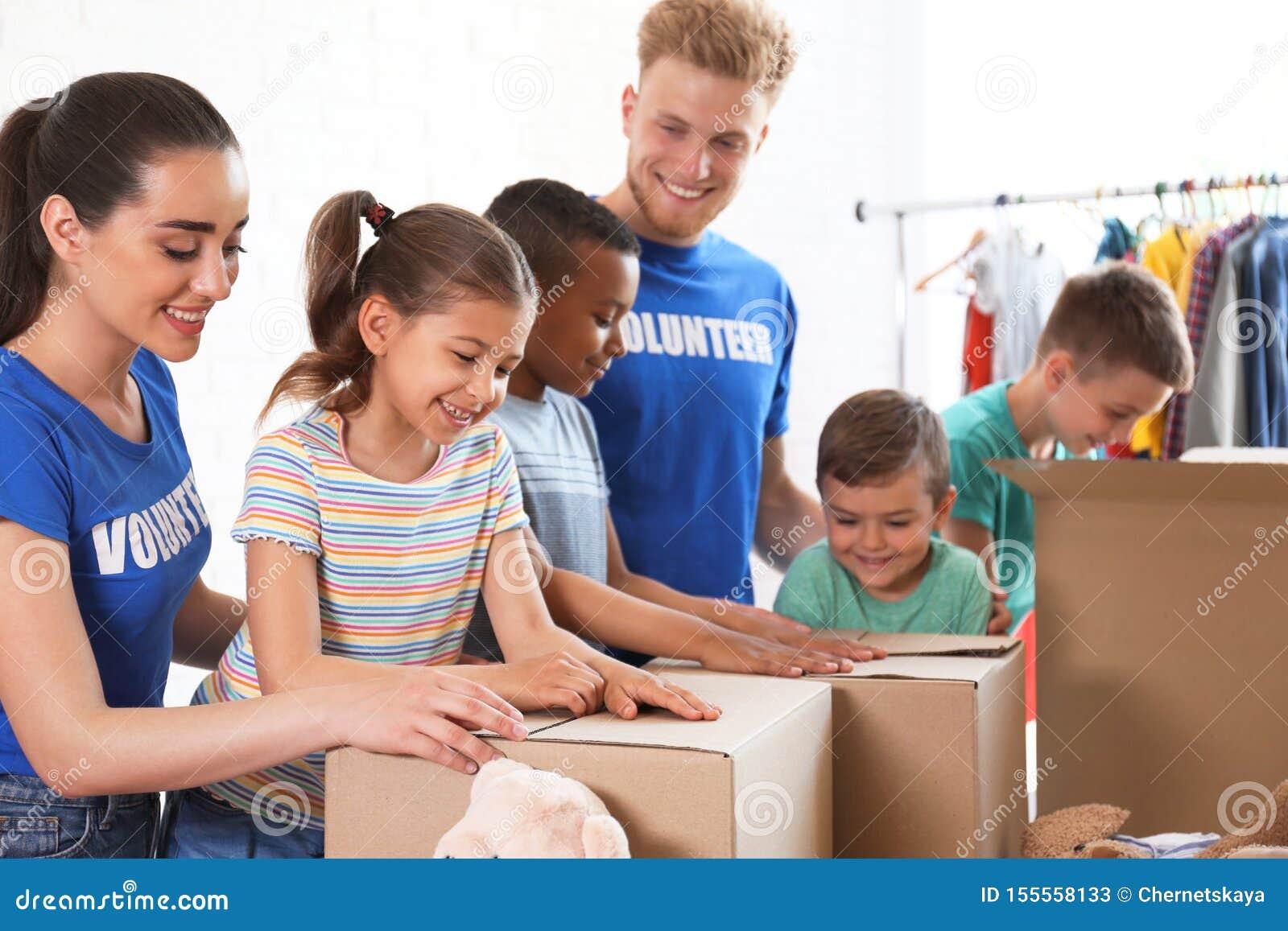 Wolontariuszi z dziecko darowizny towarami indoors