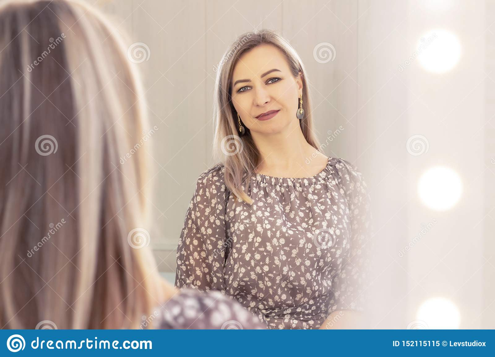 Woman aged looks in the mirror. reflection in the mirror. elderly age