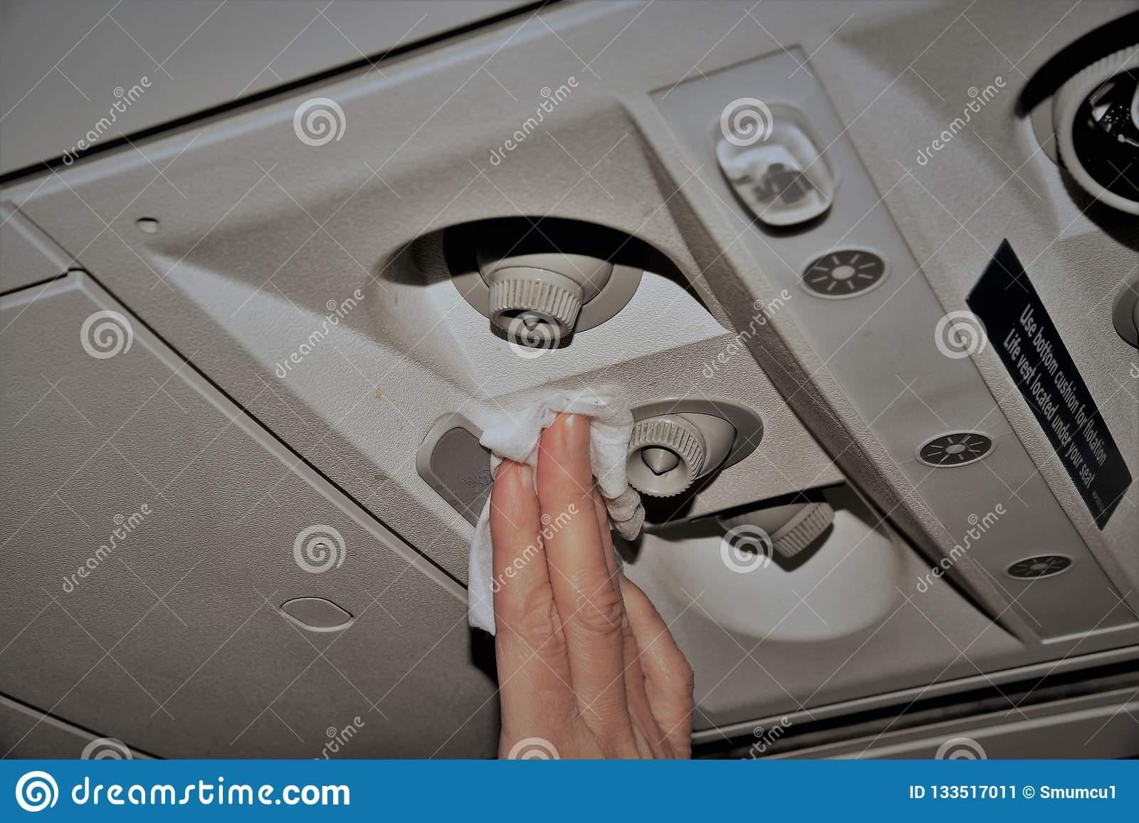 A Woman In An Airplane Cleaning The Air Vents Stock Image