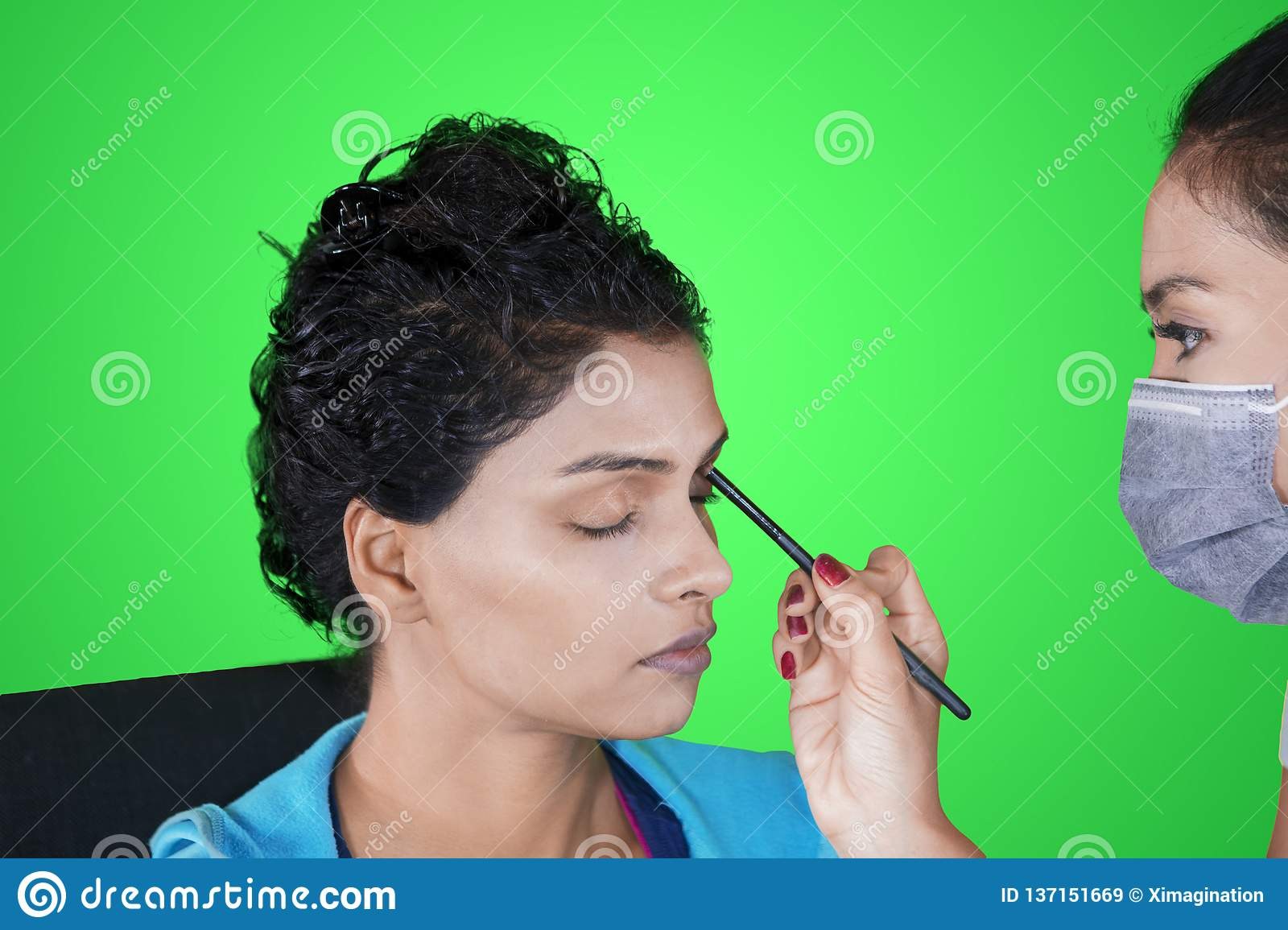 Image of India women applied eyeshadow while doing makeup with her makeup artist in the studio