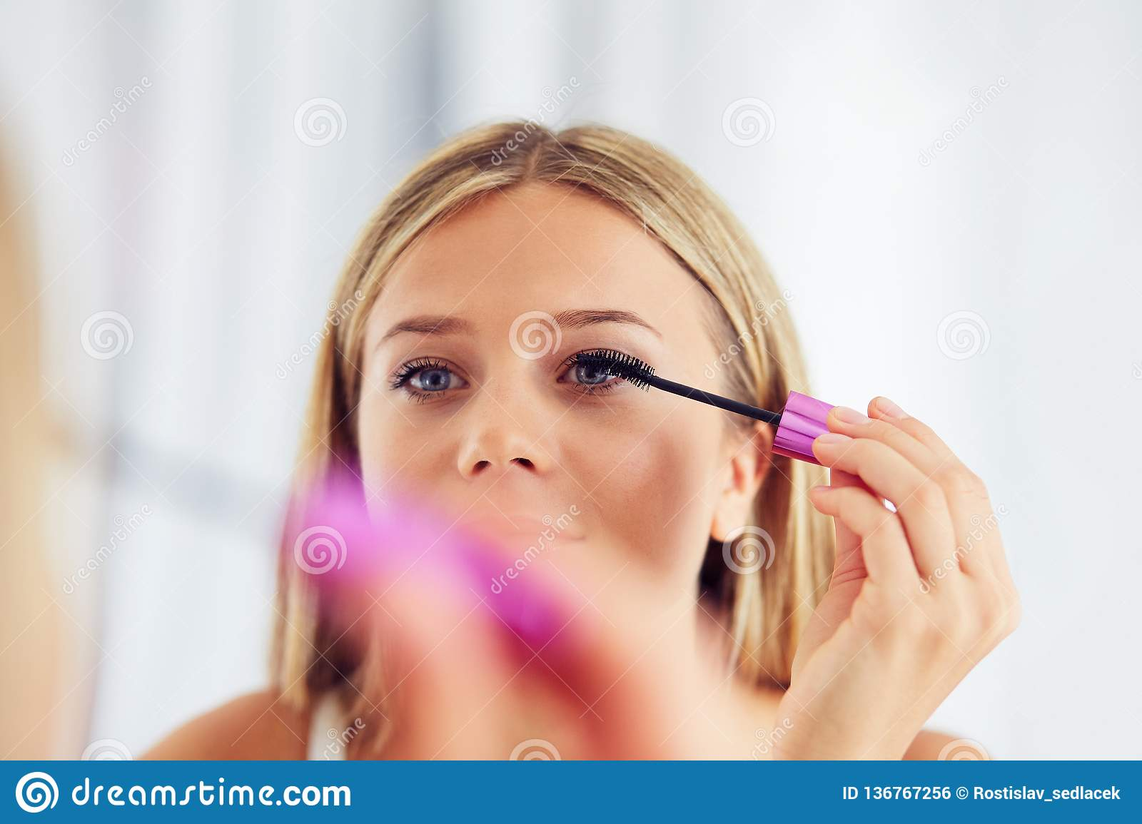Woman applying makeup and painting eyelashes with mascara