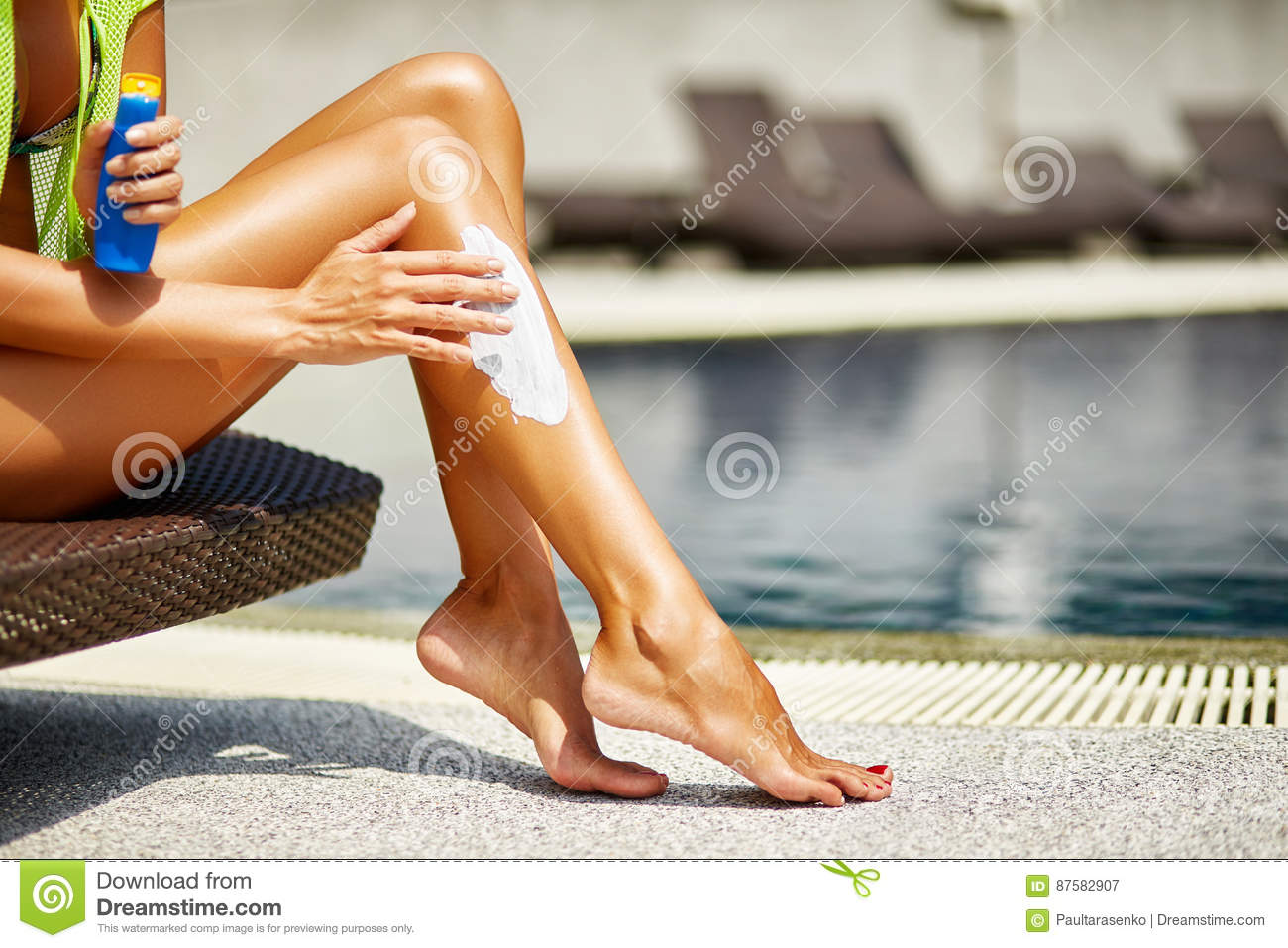 Woman applying sunscreen on her smooth tanned legs