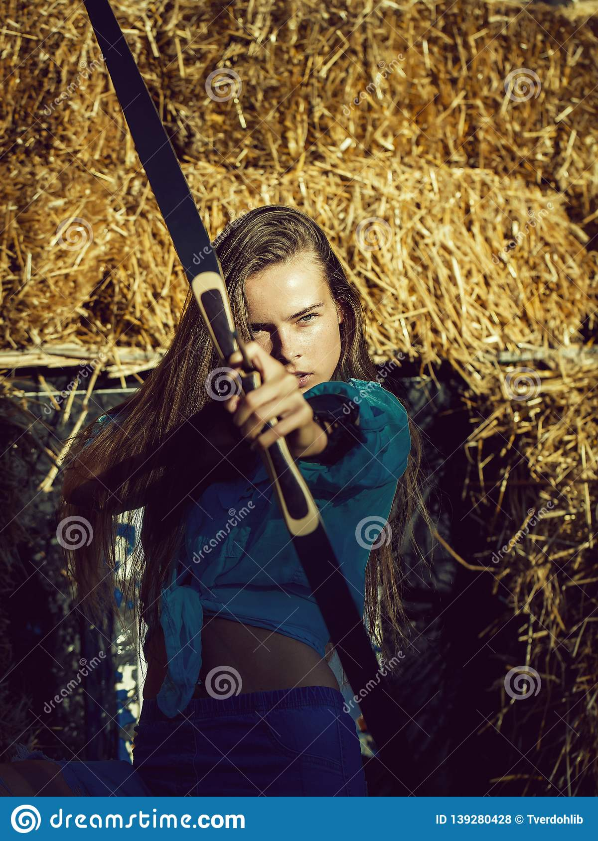 2ead88b2d59bd Woman, archer or hunter, with long hair shooting with bow and arrow on  sunny day at archery target on hay bales. Concentrate, accuracy, ambition