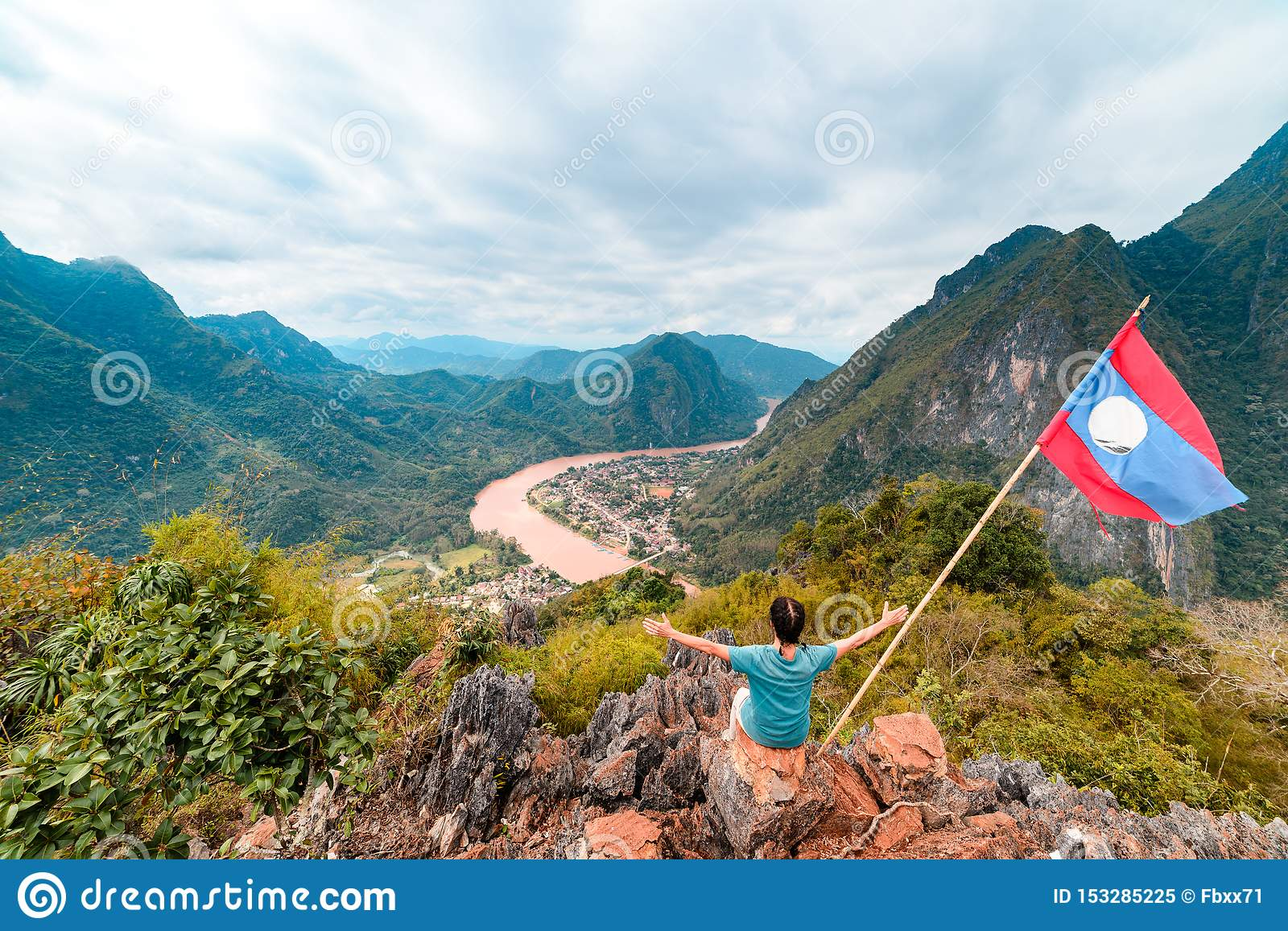 Woman with arms outstretched conquering mountain top at Nong Khiaw Nam Ou River valley Laos mature people traveling millenials