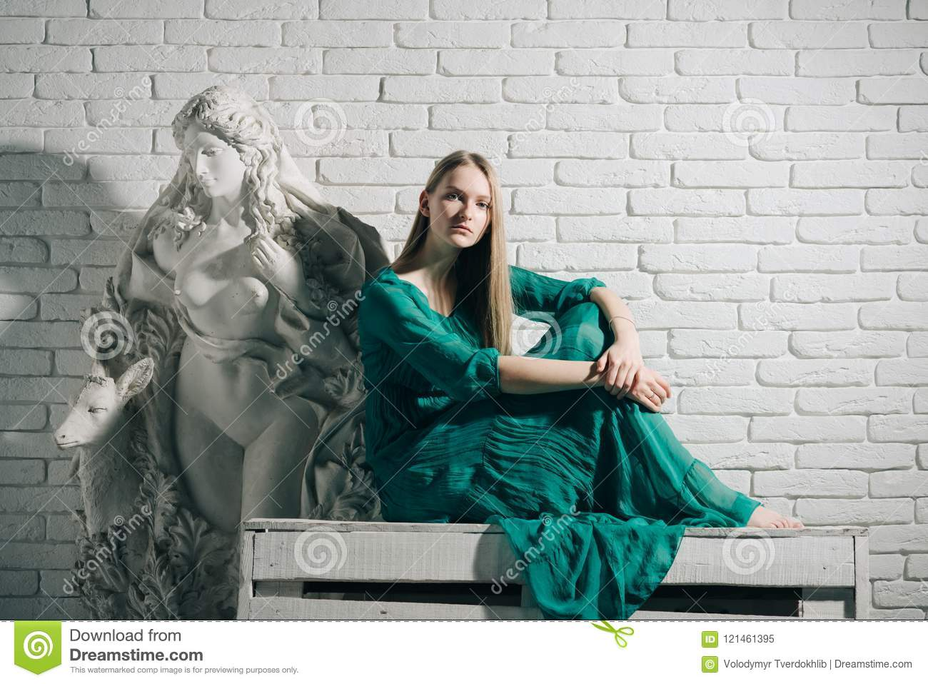 Woman artist dream and think at gypsum sculpture at workshop on white brick wall background. Art and sculpture. Art