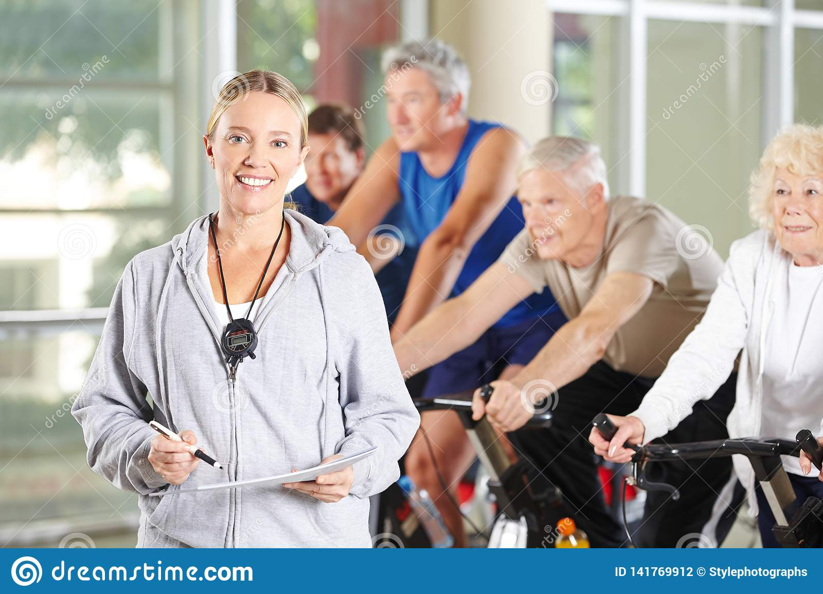 Woman as a trainer for seniors in the fitness center