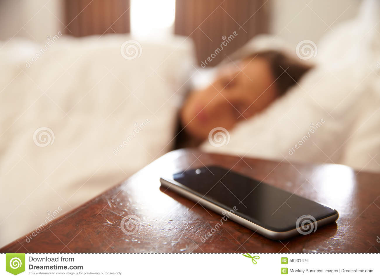 Woman asleep in bed with mobile phone on bedside table for Cell phone bed