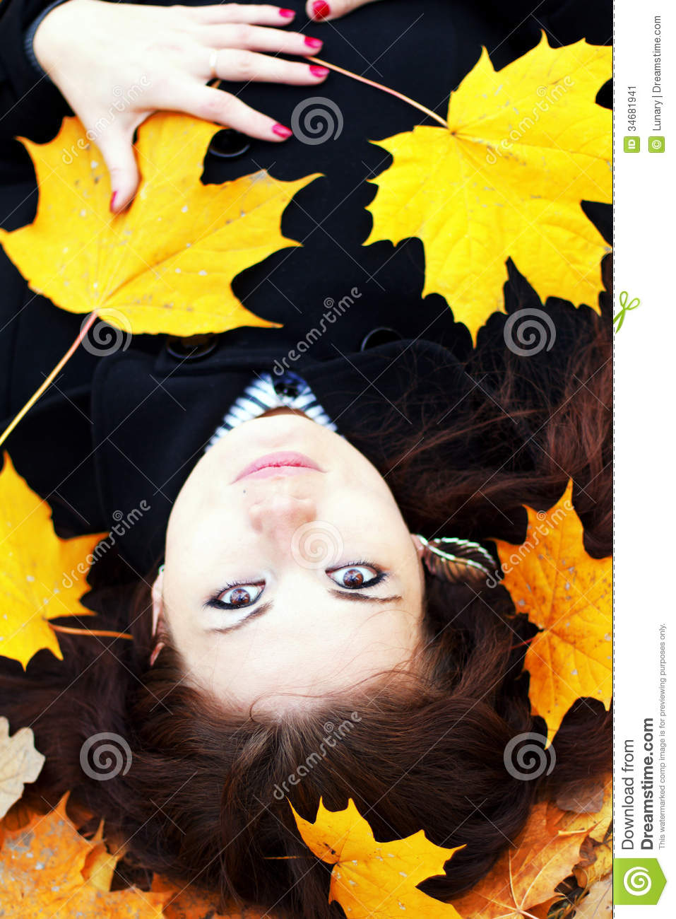 Woman in autumn orange leaves.