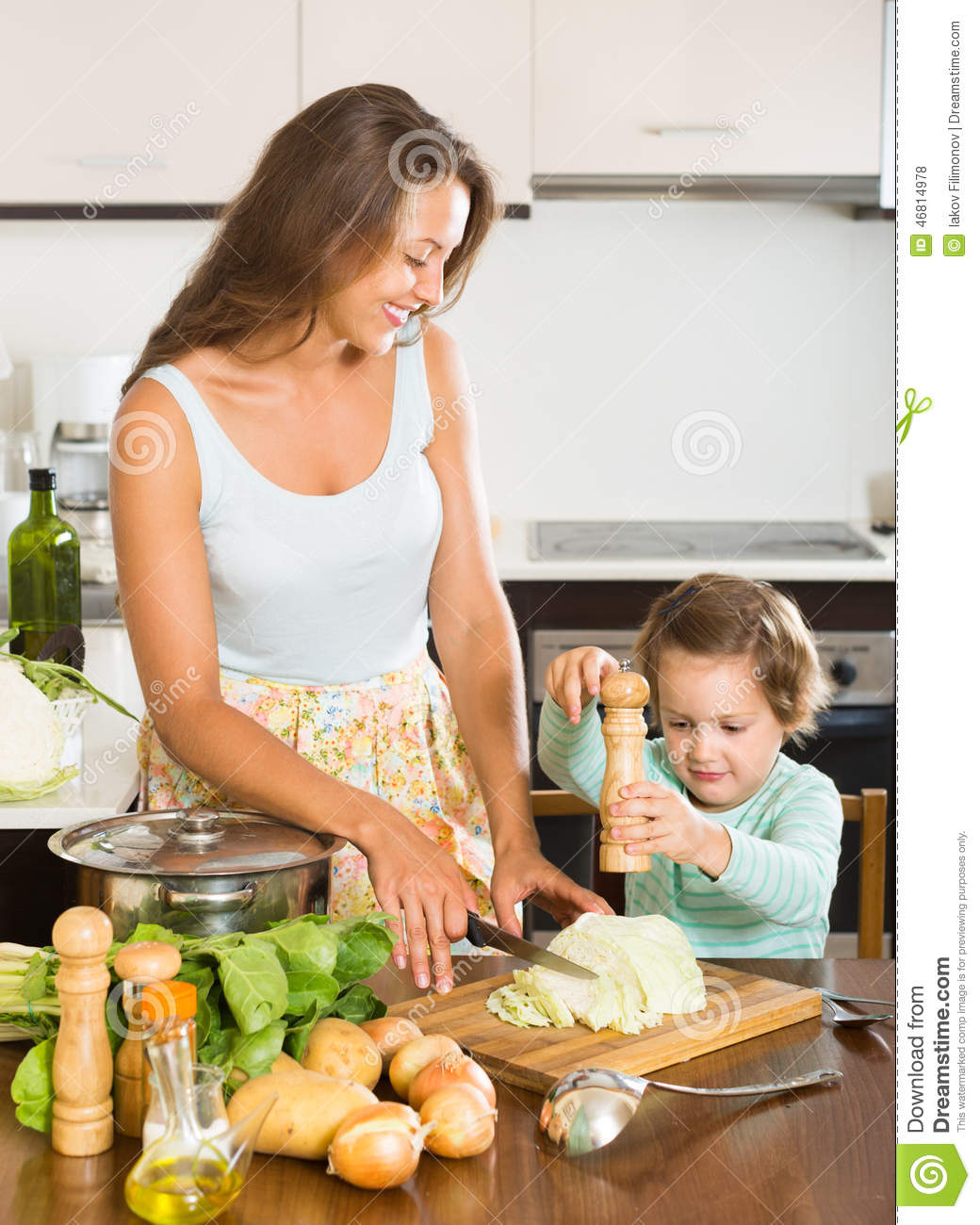 Women Kitchen: Woman With Baby Cooking At Kitchen Stock Photo