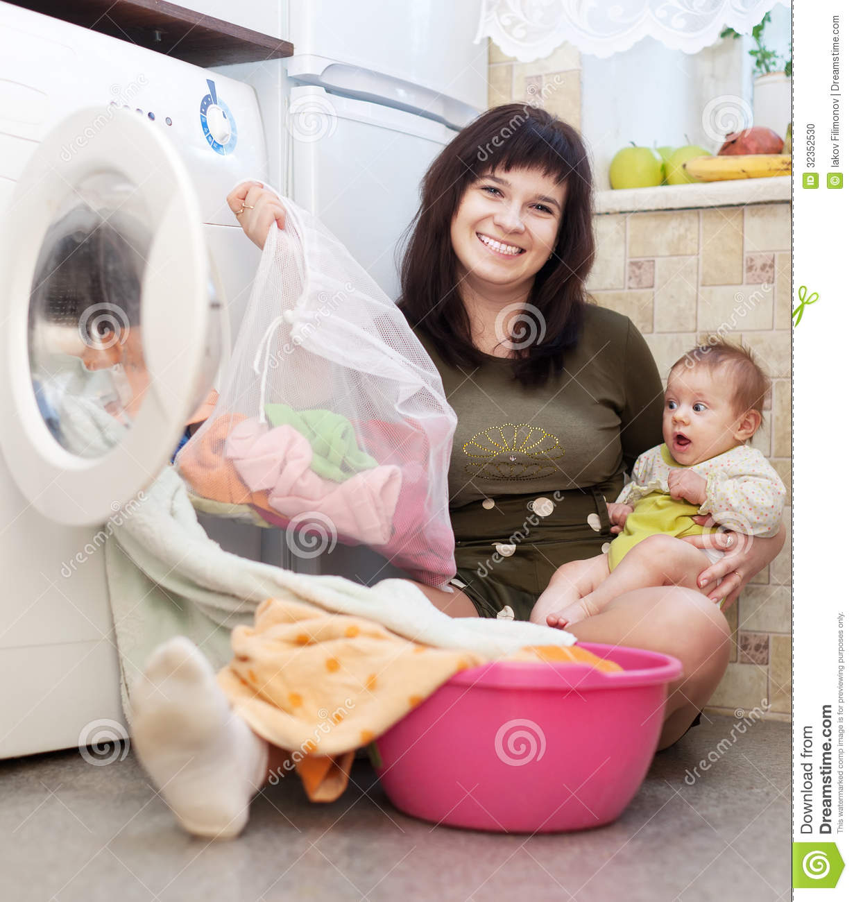 Woman With Baby Putting Clothes Into Washing Machine Stock Photo