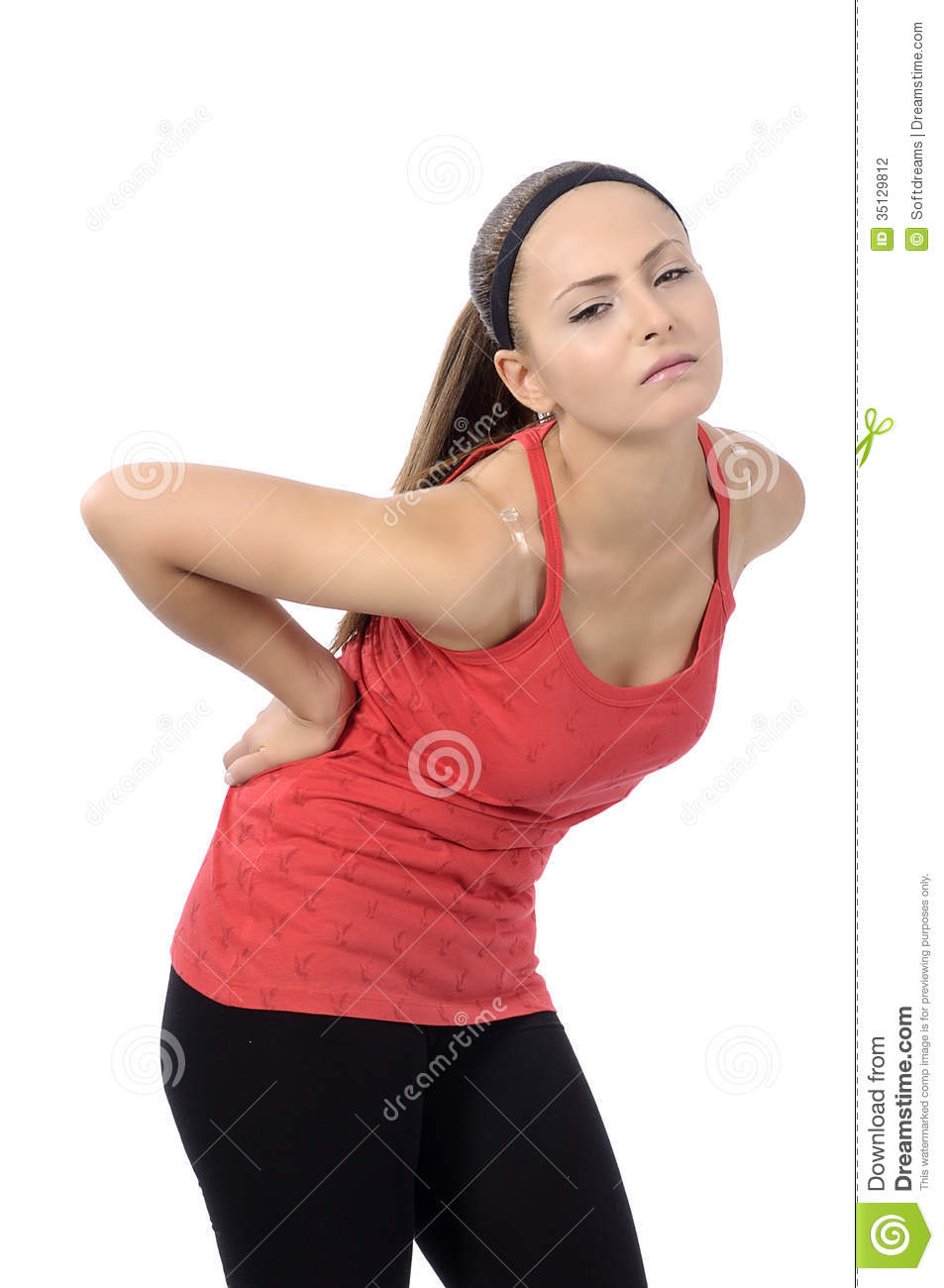 Woman bends over and flinches in pain in her back. fitness concept.