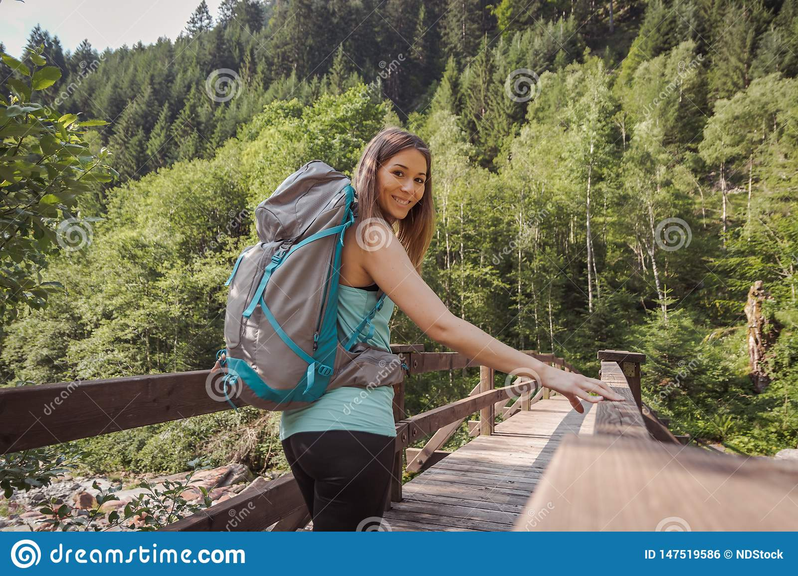 Woman with a backpack walking on a bridge into the forest