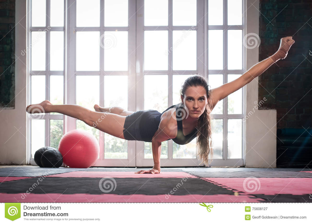 Woman balancing while doing a one hand push up showing strength