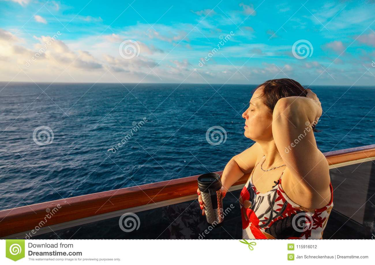 Woman on the balcony of a cruise ship at sunrise