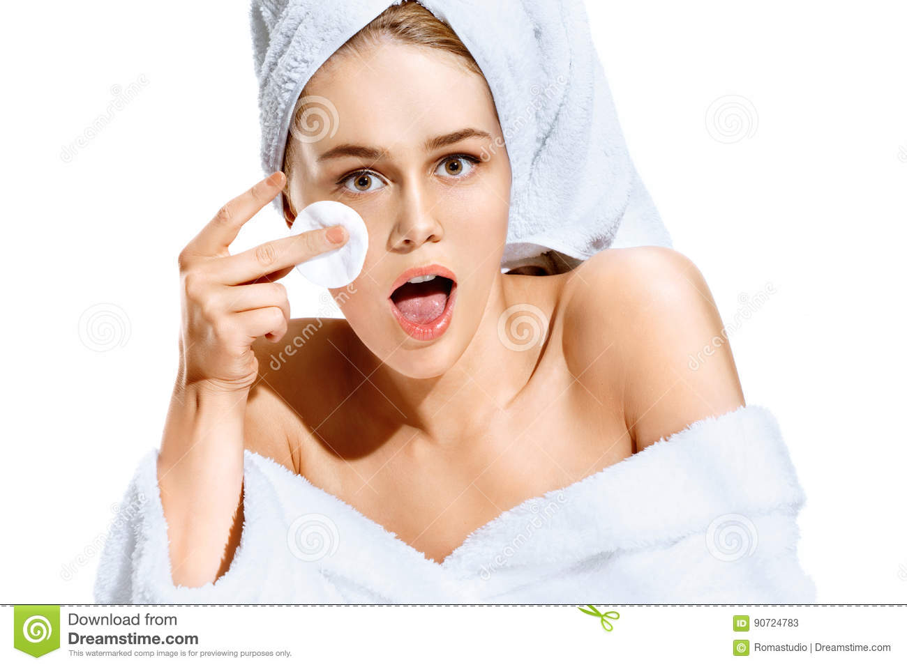 Woman after bath in white bathrobe and towel on her head cleaning her face with cotton pad