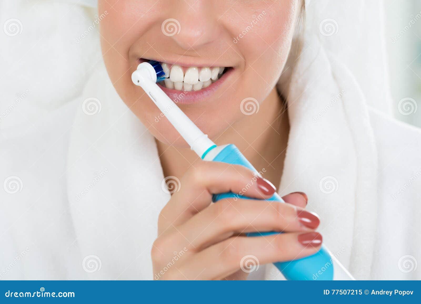 Woman In Bathrobe Brushing Teeth With Electric Toothbrush