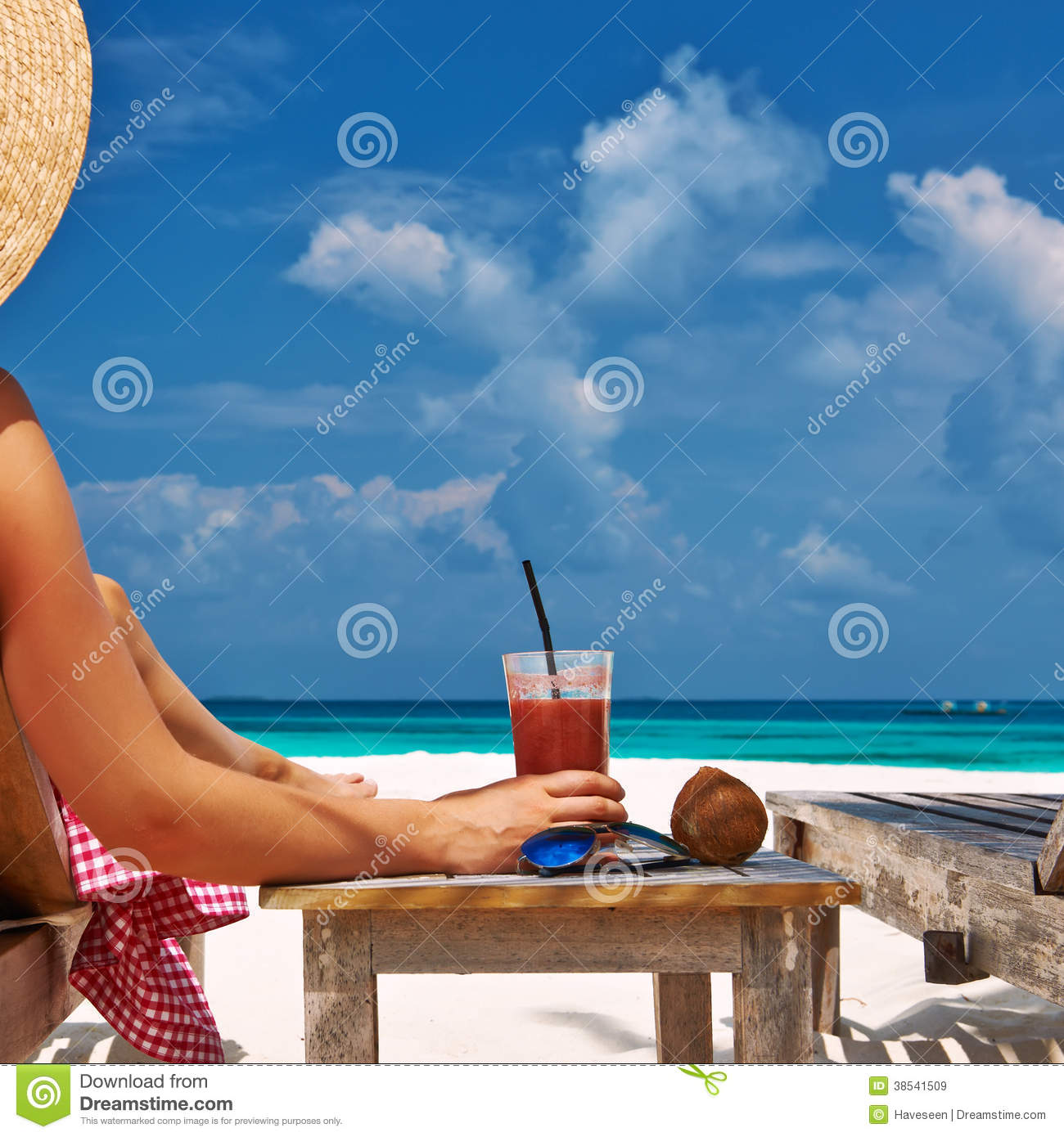 Woman at beach with chaise-lounges