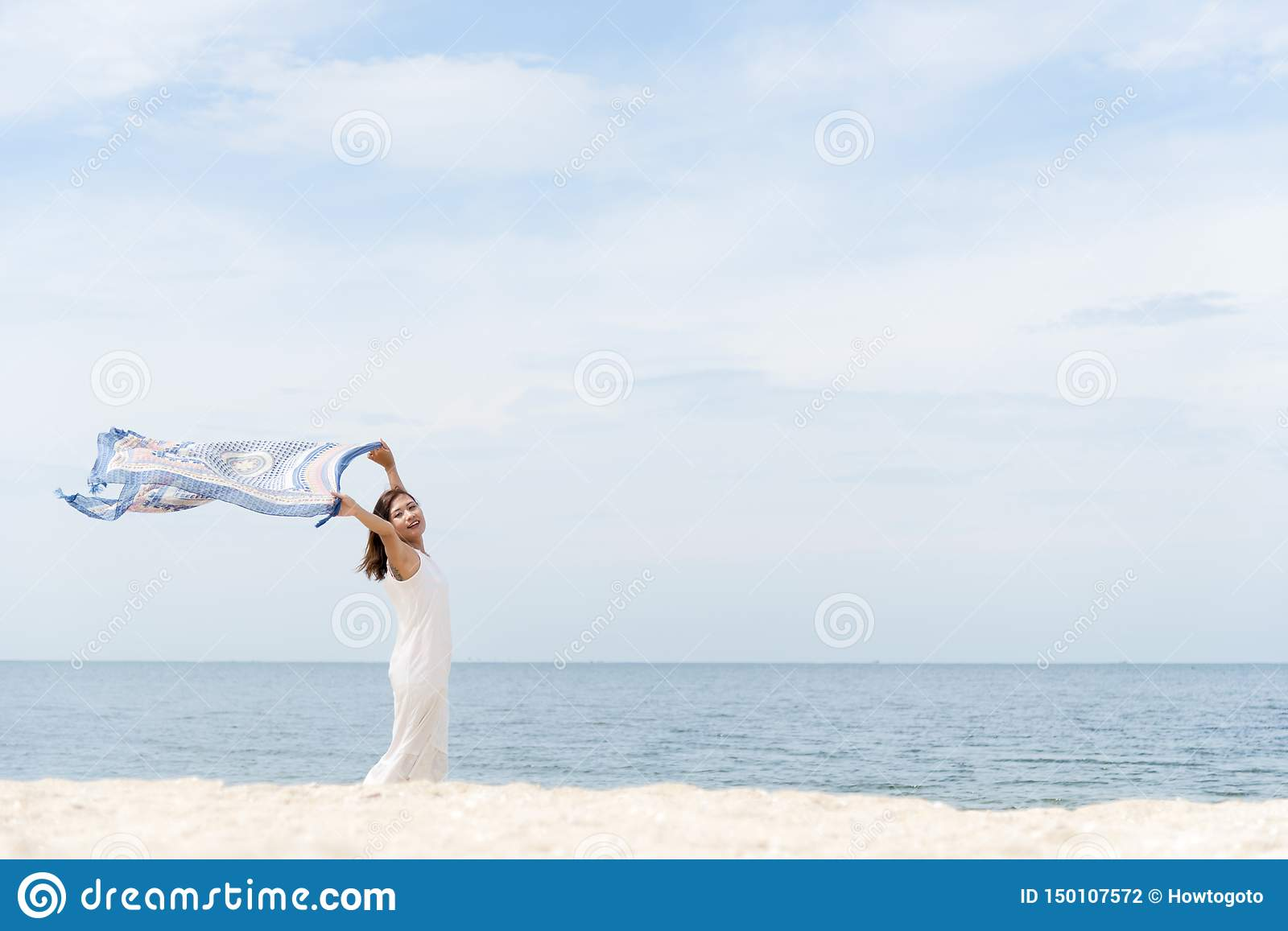 Woman on the beach, portrait of young happy woman wearing white dress and holding scraft on tropical sand beach. Summer Concept
