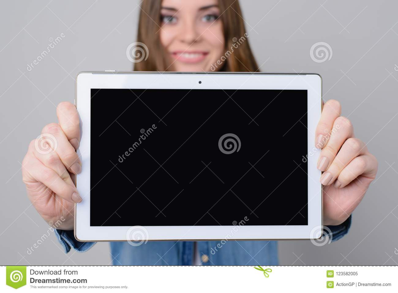 Woman with beautiful face, toothy smile is showing digital tablet with empty black screen. Close up photo, isolated on grey backgr