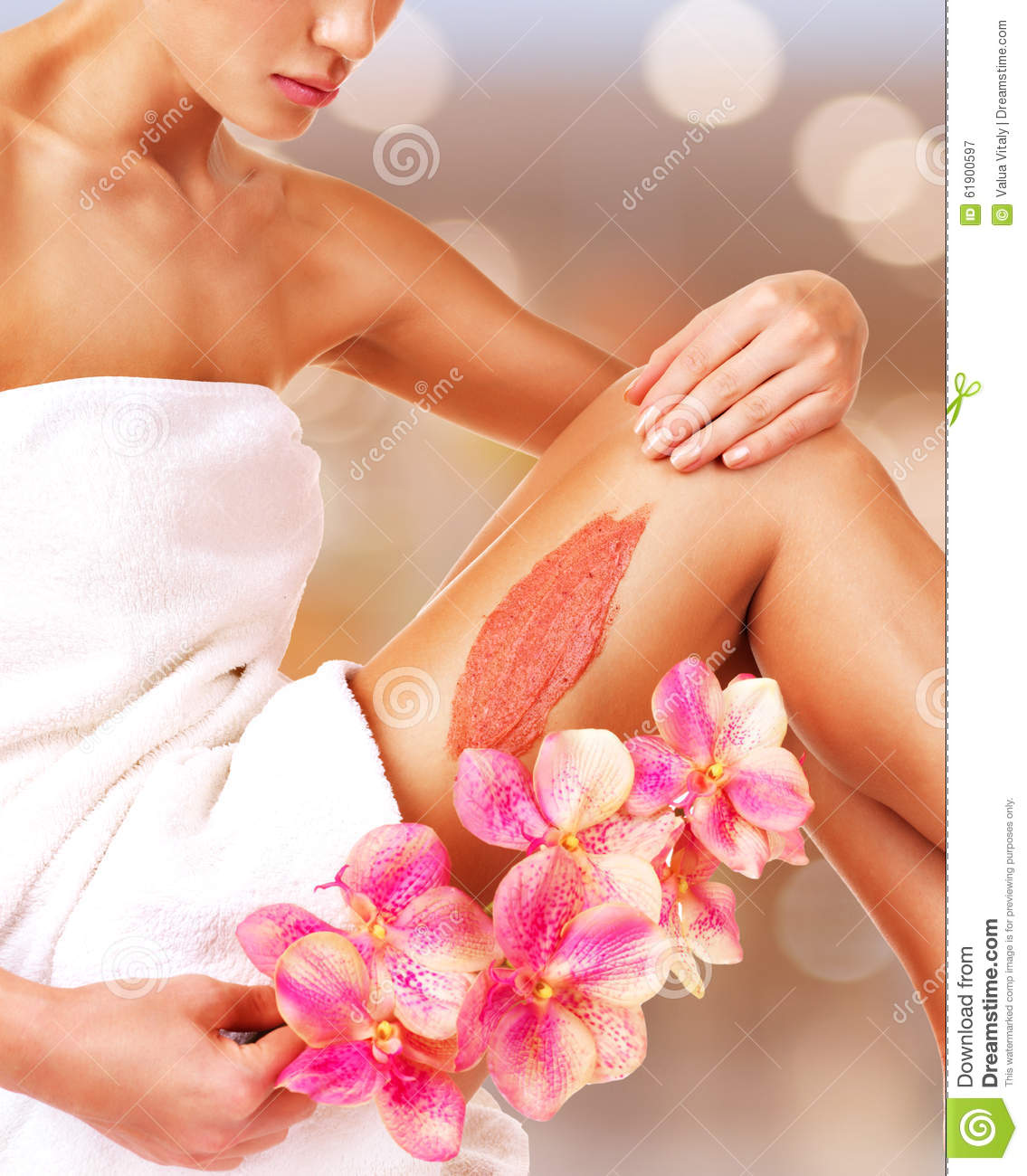The woman with a beautiful with flowers body using a scrub