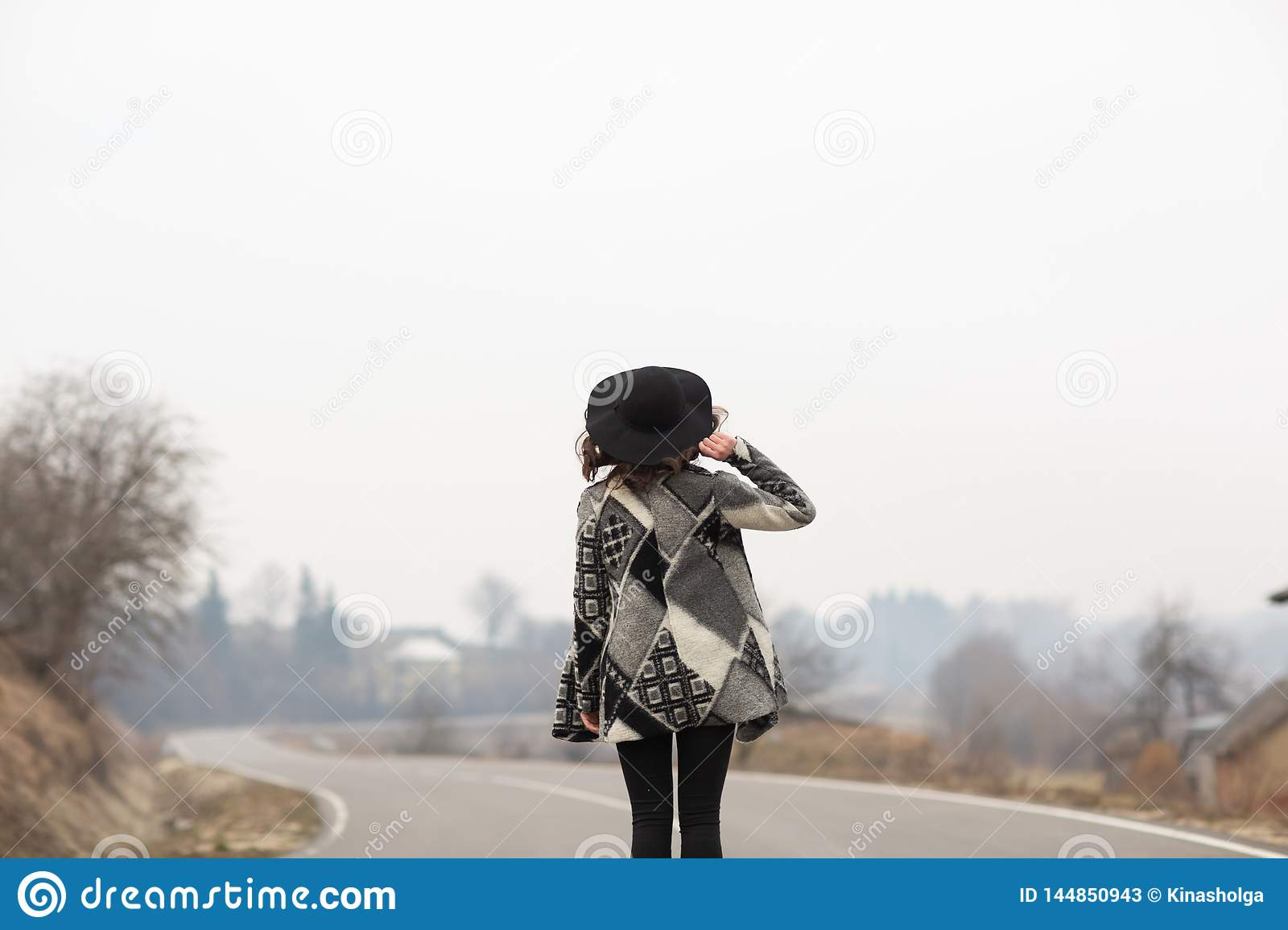 A woman in a beautiful gray cardigan and black hat rides along the way. Back view