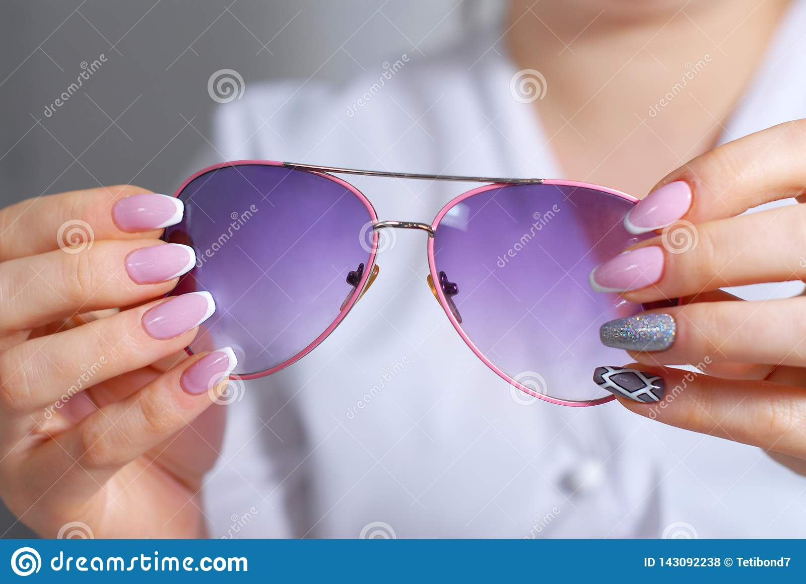 Woman`s hands with a beautiful manicure examines sunglasses