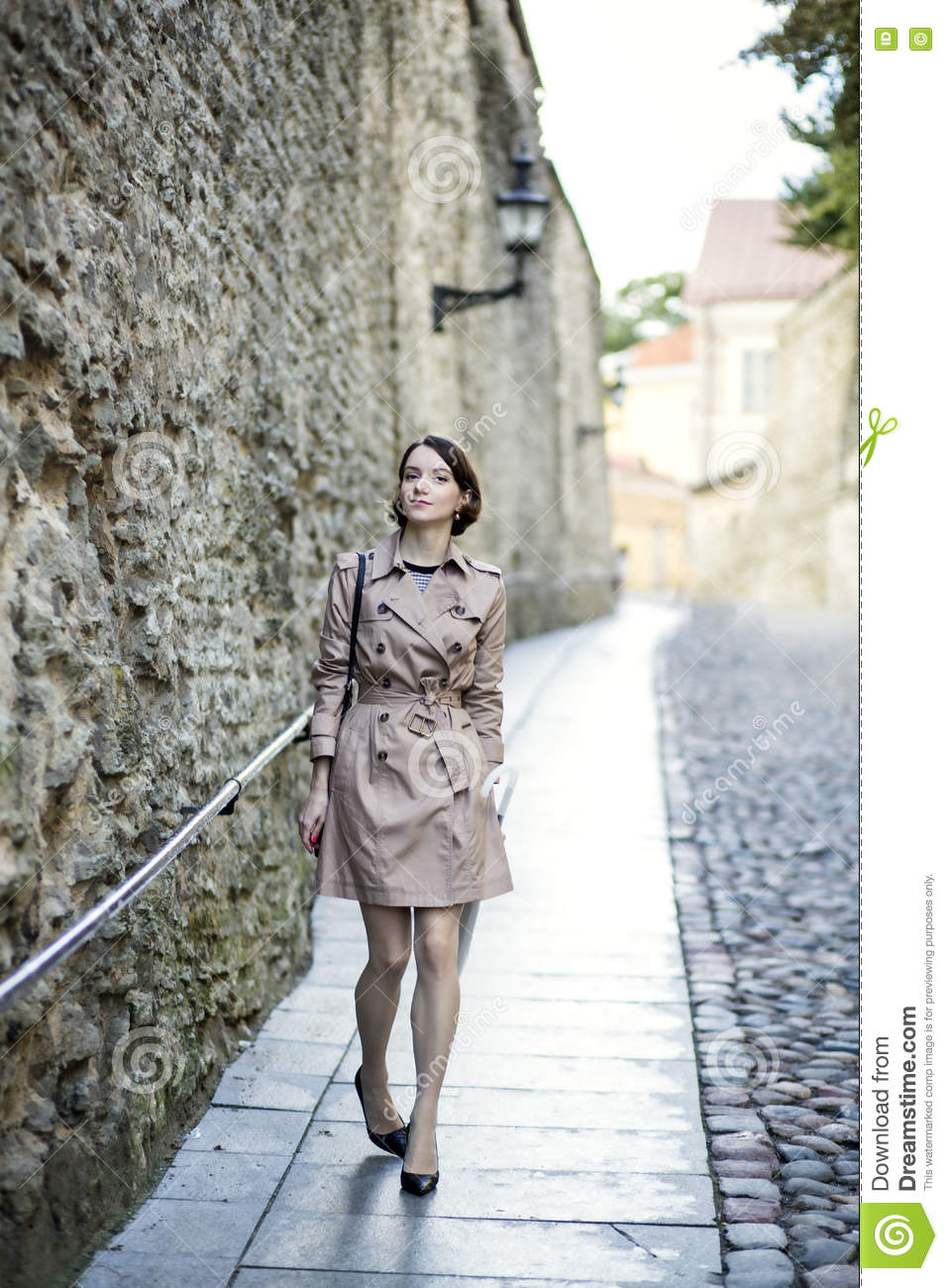 Woman at beige coat near old city wall