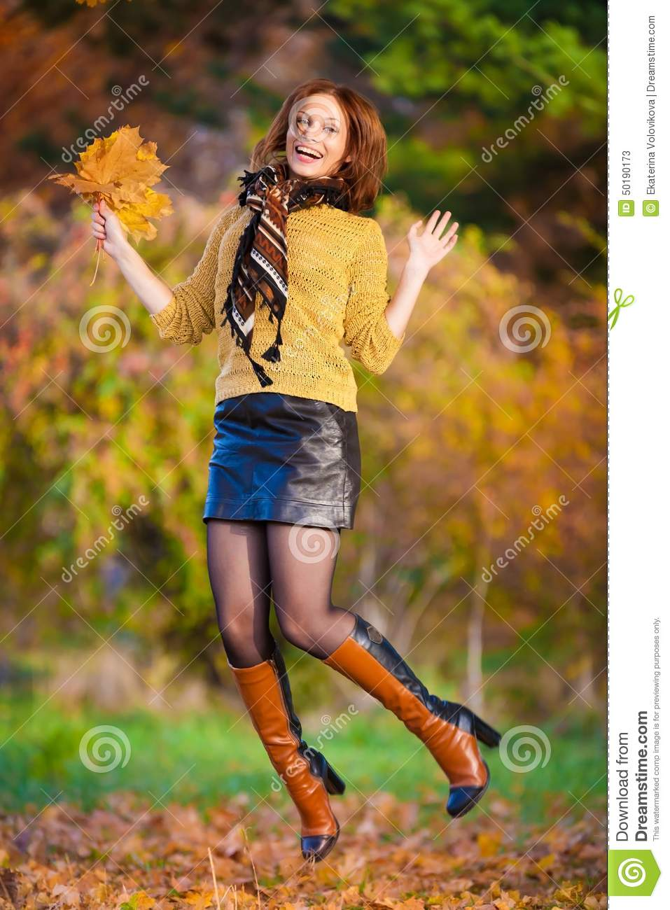Woman In Beige Sweater And Black Leather Skirt Jump Stock