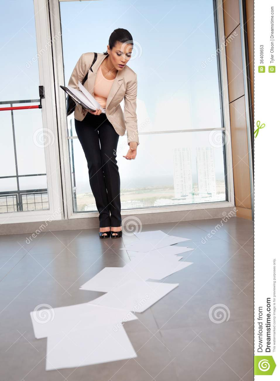 Woman bending down to collect papers on floor stock image for Down to the floor