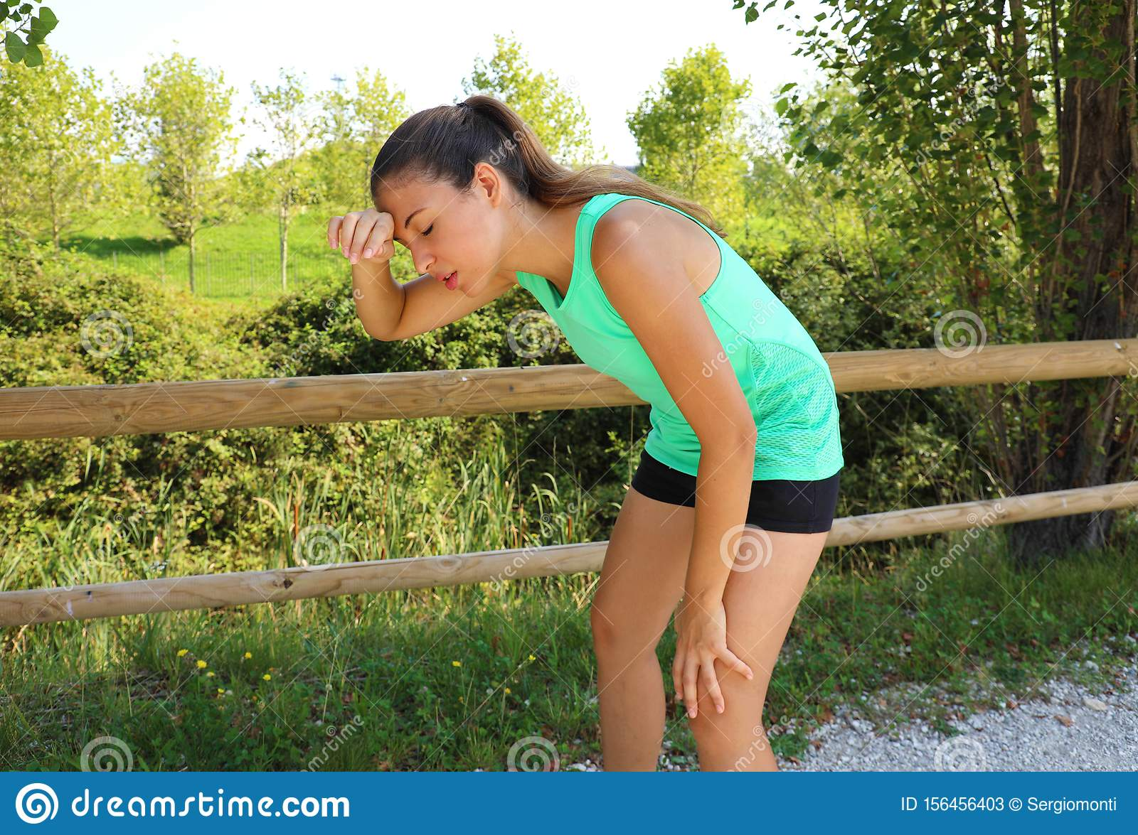 Woman bent over in exhaustion and catching her breath after a running session