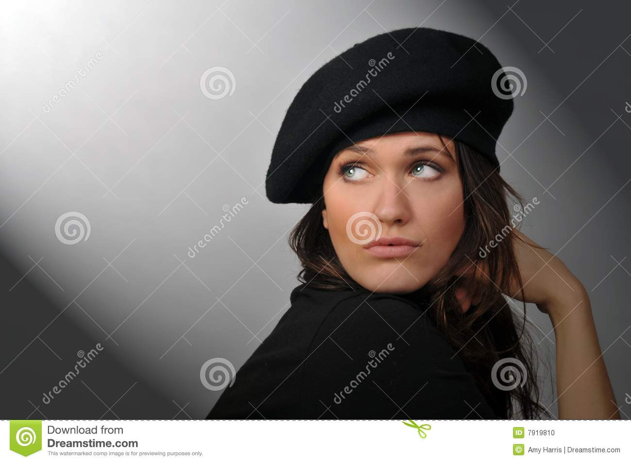 Portrait of beautiful brunette woman with beret looking back over shoulder  into beam of light. 59404c2864e