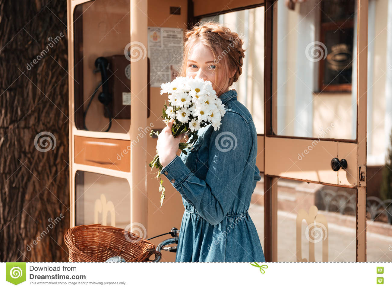Woman with bicycle and bouquet of camomiles standing on street