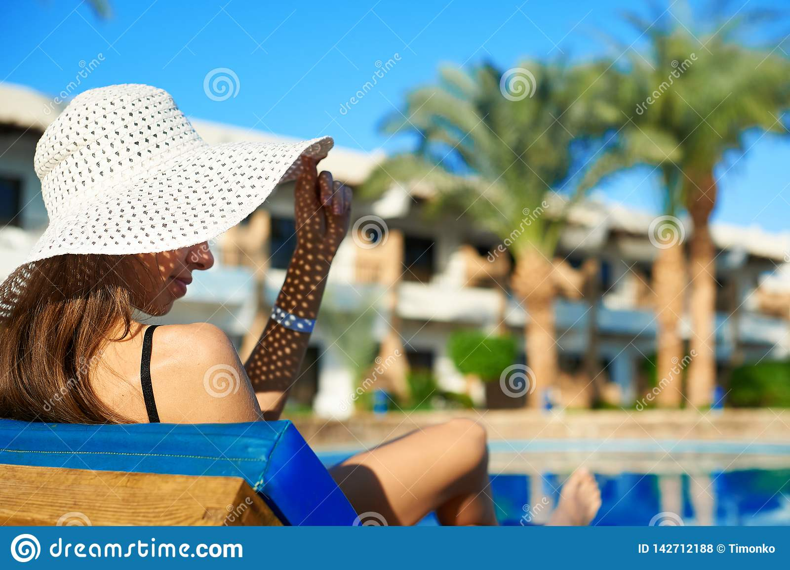 Woman in big white hat lying on a lounger near the swimming pool at the hotel, concept summer time to travel in Egypt