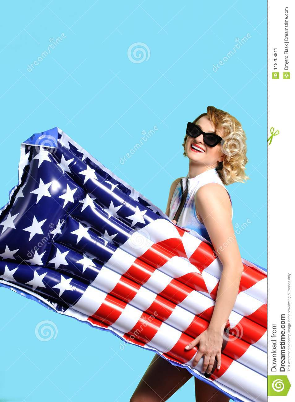 a6b1c4c1ce Enjoying suntan woman in bikini with inflatable mattress american flag on  the beach.