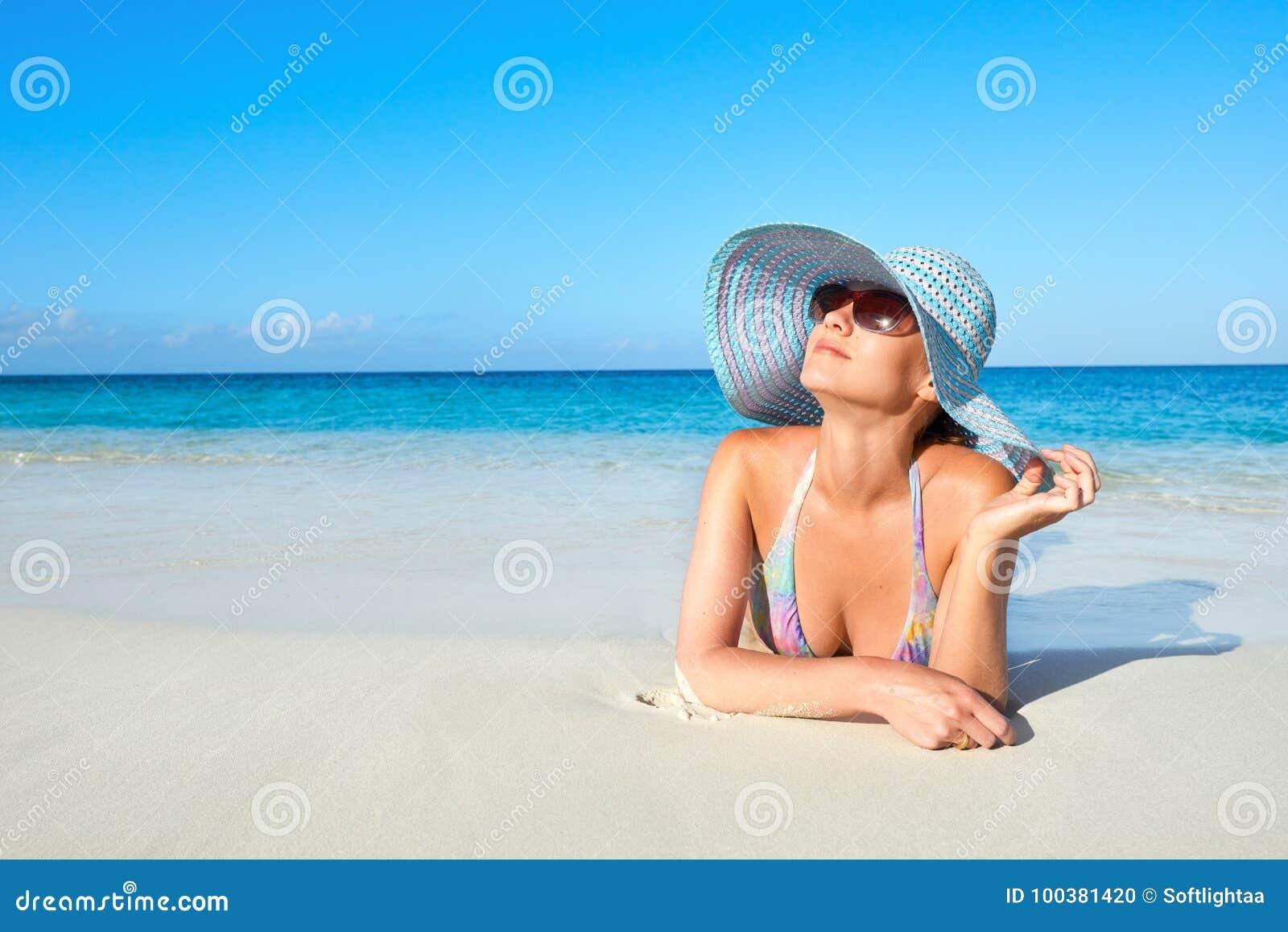 Woman in bikini and summer hat enjoying on tropical beach